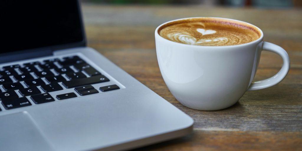 Caffè a fianco della tastiera di un MacBook